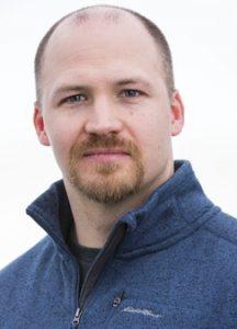 Portrait of Adam Williams against a white background.